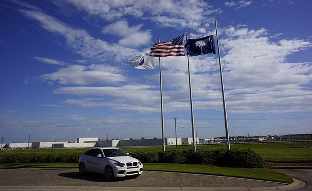 a car parked with three flag poles standing near it